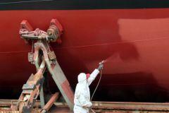Aplicador pintando el casco de un barco